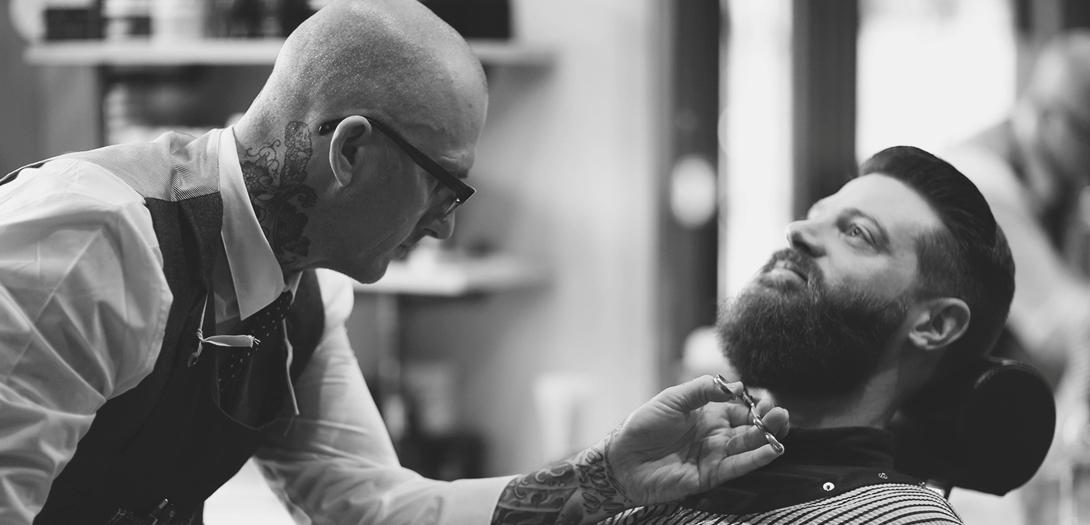 мужчине стригут бороду